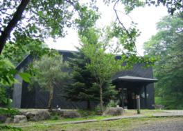黒塗りの五角形の建物が森の中に佇む