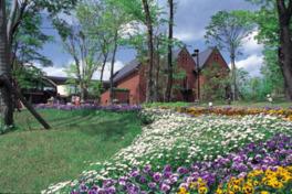 四季の花が咲き乱れ、緑に包まれた高原リゾートに位置する