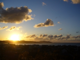 綿のように流れる雲の間から昇る朝日
