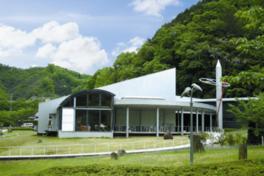青い緑の森を背に佇む美術館