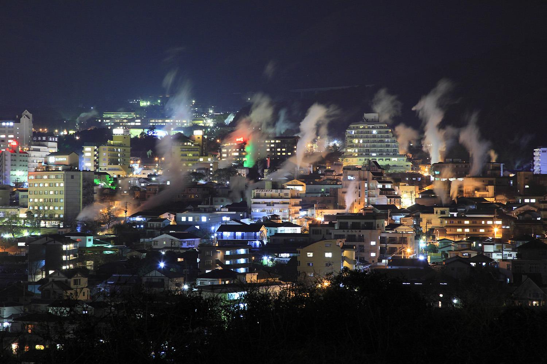 扇山や鶴見岳を背景に湯けむりと温泉街の明かりが際立つ