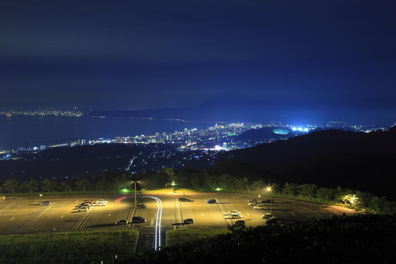 高崎山のシルエットを背景に別府湾沿いに街明かりが広がる