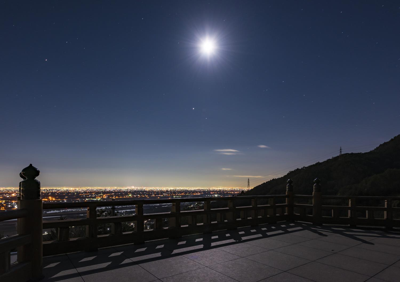きらびやかな街の灯りと静かな月の対比も美しい